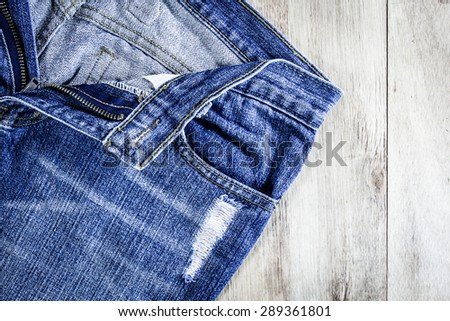 Blue jeans on old wooden background. - stock photo