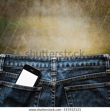Blue jeans with cell phone in a pocket on vintage background