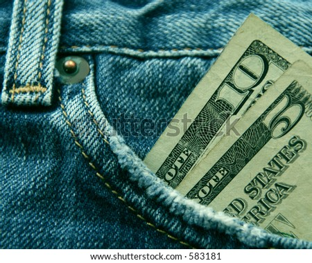 Blue jeans with fifteen American dollars in the front pocket. - stock photo