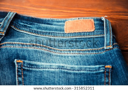 blue jeans with half of back pocket and brown leather tag on wood table background. Shallow depth of field.  - stock photo