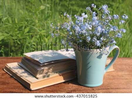 Blue jug with bouquet of forget-me-nots on wooden table and the opened books - stock photo