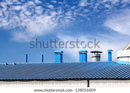 Blue kitchen chimneys on top of the roof - stock photo