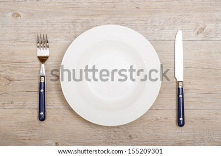 Blue knife and fork with white plate on  a dinner table - stock photo