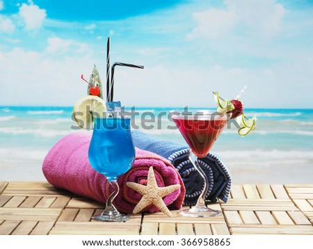 Blue lagoon and strawberry daiquiri cocktails on the beach - stock photo