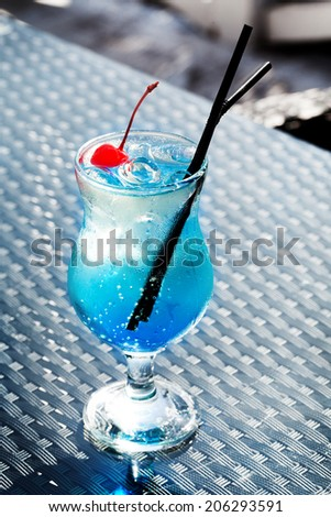 Blue Lagoon cocktail with a cherry in a still life - stock photo