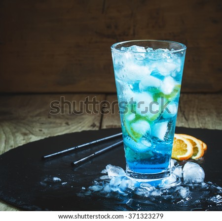 Blue Lagoon cocktail with orange and ice in a tall glass, dark toned image, selective focus - stock photo