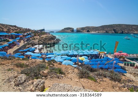 BLUE LAGOON, COMINO, MALTA - SEPTEMBER 16, 2015: Visitors crowd to enjoy the clear turquoise water of Blue Lagoon under  umbrellas on a sunny day in September 16, 2015 in Comino island, Malta.