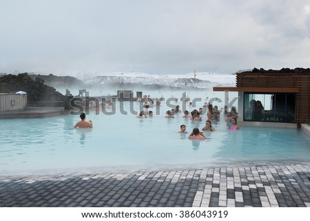 BLUE LAGOON, ICELAND - February 20, 2016: People bathe in the open air SPA in winter, drinking cocktails near the bar. The Blue Lagoon geothermal spa is one of the most visited attractions in Iceland. - stock photo