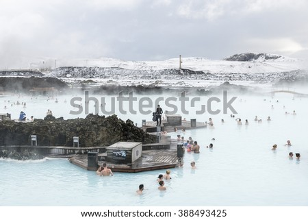 Blue lagoon, Iceland - February 20, 2016: People in thermal spring are drinking cocktails near  a cafe on the water, SPA centre Blue lagoon in winter. - stock photo