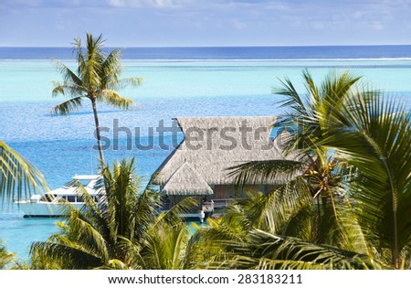 Blue lagoon of the island of Bora Bora, Polynesia. A view from height on palm trees, traditional lodges over water and the sea - stock photo