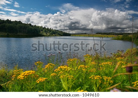 Blue lake and yellow flowers - stock photo