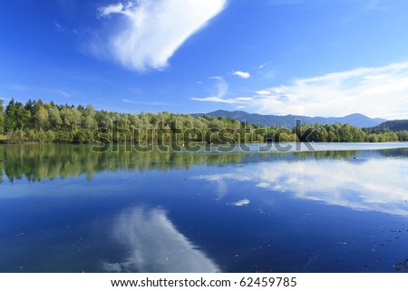 blue lake with colorful wood and blue sky in autumn - stock photo