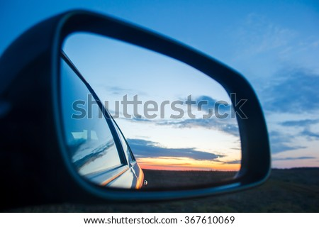 Blue landscape sunset reflect in mirror of car - stock photo