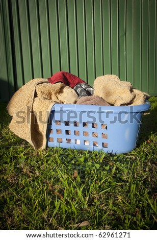 Blue laundry basket filled with towels sits on a lawn outside - stock photo