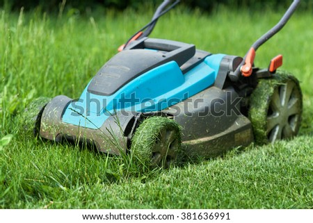 Blue lawnmower cutting grass, with fresh cut strip in the foreground - closeup - stock photo