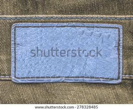 blue leather label on brown jeans background - stock photo