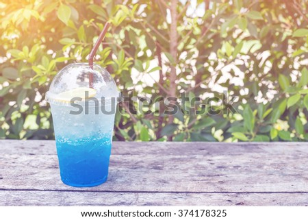 blue lemon soda on wood table with green leaves background, be fresh in nature pastel tone - stock photo