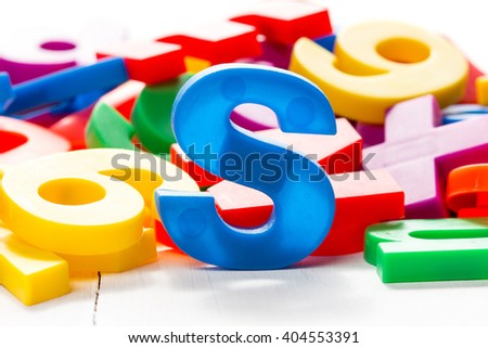 Blue letter S in a front of other colorful plastic letters.