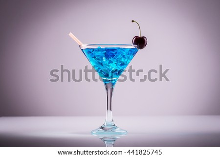 Blue light alcoholic cocktail with ripe cherry on the edge of the glass - stock photo