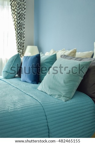 Blue, light blue and beige pillows on bed in blue wall bedroom