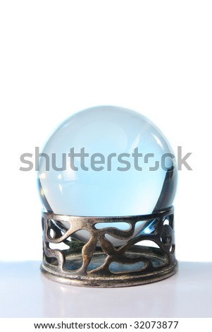 Blue light in a crystal ball in stand against a white background - stock photo