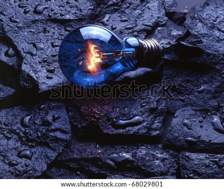 Blue light lamp bulb lye upon wet rocks - stock photo