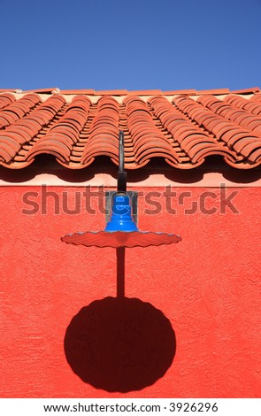 Blue light with a colorful adobe wall and southwest shingles against a deep blue sky in Tucson, AZ - stock photo