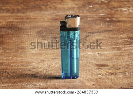blue lighter on the table - stock photo