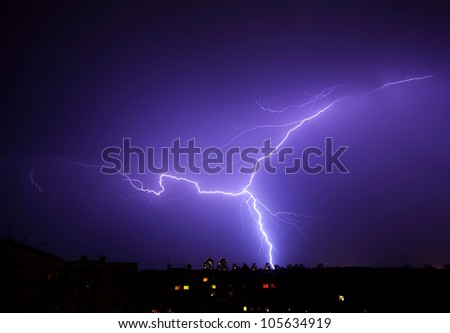 Blue lightning bolt strikes in the night skies - stock photo