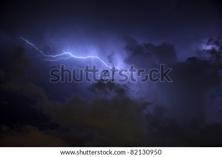 Blue Lightning strike surrounded by storm clouds and rain columns - stock photo