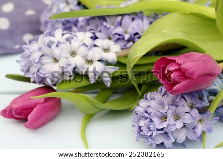 Blue, lilac hyacinth and dusky pink tulips i on wooden pale duck egg blue painted wooden boards , pretty spring image , shallow depth of field , mothers day  - stock photo
