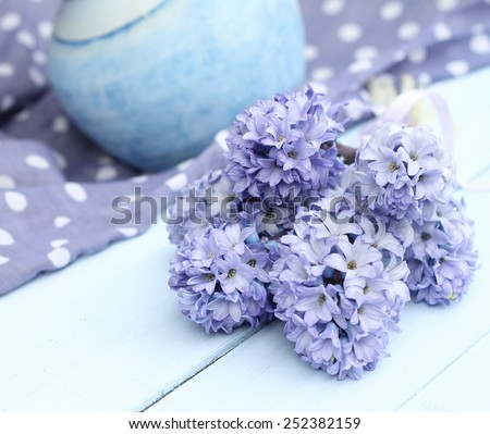 Blue lilac hyacinth on wooden pale duck egg blue painted wooden boards ,dusky blue ceramic vase and spotty periwinkle fabric in background, pretty spring image , shallow depth of field , mothers day - stock photo