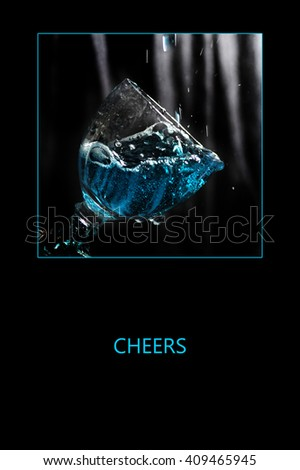 """Blue liquid in glass against dark textile background. Frame and the word """"CHEERS"""" on black. - stock photo"""