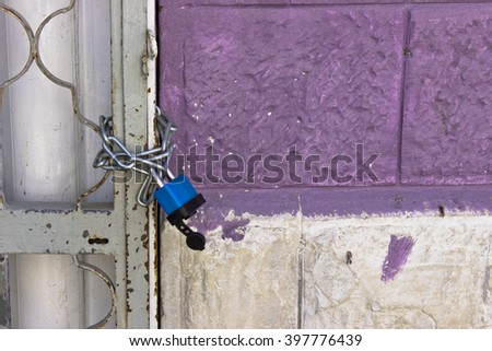 blue lock in a gate next to a purple wall.