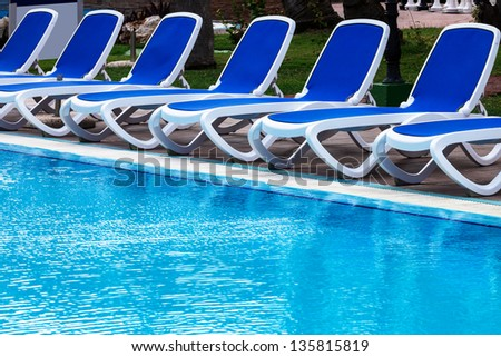 blue lounge chairs by the pool - stock photo