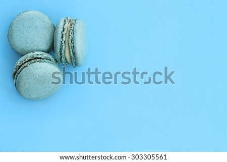 Blue macarons over blue background with room for copy space.