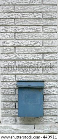 blue mail box on white brick wall - stock photo