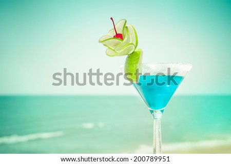 Blue margarita cocktail with lime fruit and cherry decoration at tropical ocean beach. Vintage style, hipster colors image with copy space for party invitation text  - stock photo