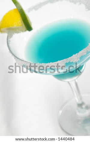 Blue margarita garnished with sugar, lemon and lime. - stock photo