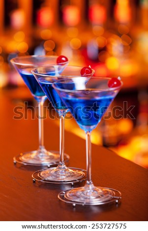 Blue martini cocktail on a bar - stock photo