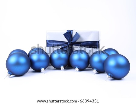 Blue matt christmas balls and a gift in red wrapping on white background, with space for your text - stock photo