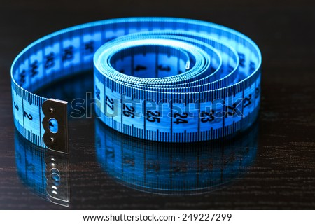 blue measuring tape laying on black reflective background - stock photo