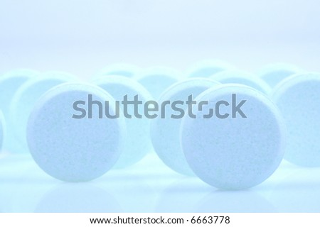 Blue medicine pills on light blue background - stock photo