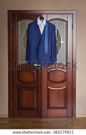 Blue men's suit hanging on a door - stock photo