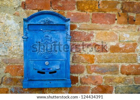 Blue metal mailbox on a brick wall in Monteriggioni, Tuscany, Italy. - stock photo