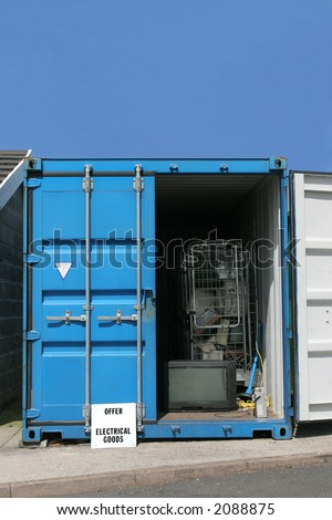 Blue metal recycling container for electrical goods, set against a blue sky.