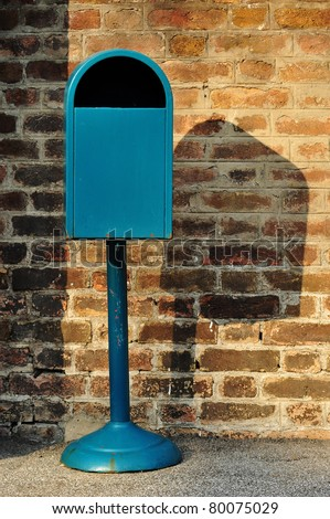 Blue metal trash can against a brick wall - stock photo