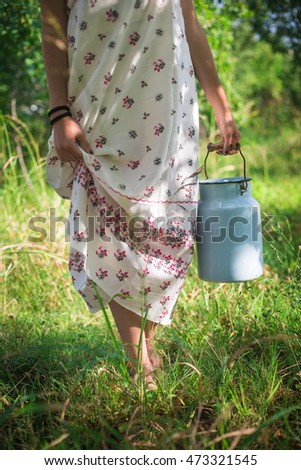 Blue milk can carried by a barefoot young woman holding her country-style dress hem