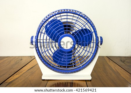 Blue mini fan on wooden floor - stock photo