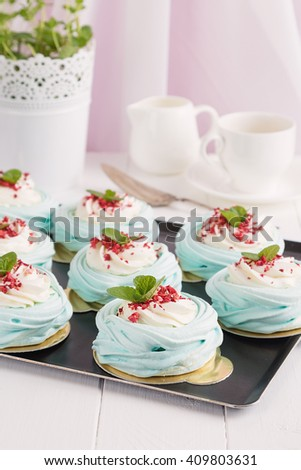Blue mini pavlova meringue cakes with cream cheese on white background. Shallow focus